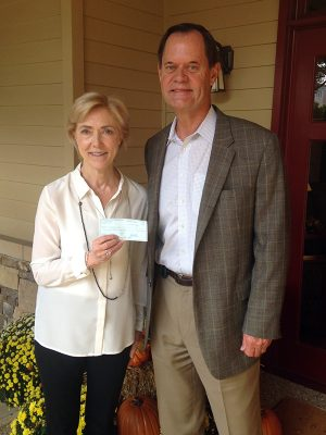Charlie Caswell delivers check to Sally Hale the Executive Director of Camp Sunshine